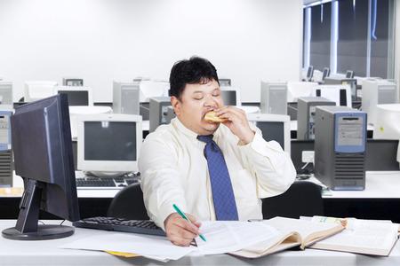 eten: Obesitas zakenman werken in functie, terwijl het eten van junk food