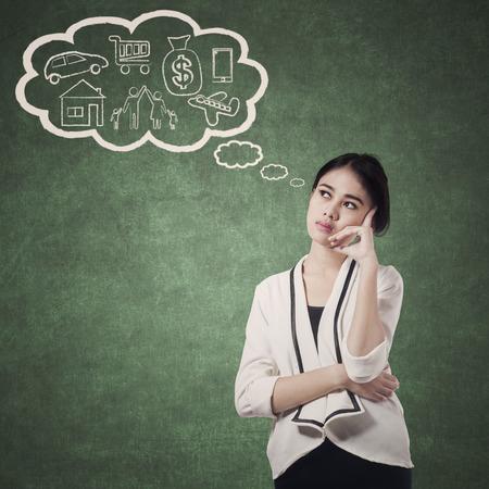 mujeres pensando: Mujer bonita que la planificaci�n de su futuro pensando que su plan Foto de archivo
