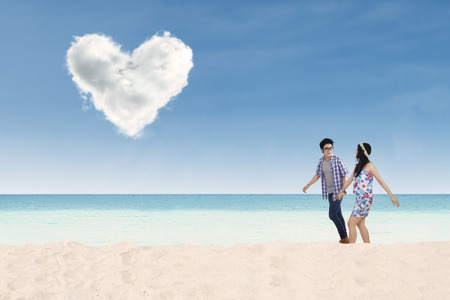 Romantic young couple walking together on the beach while holding hands with heart shaped cloud photo