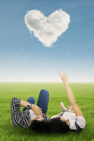 heart under: Couple enjoy holiday under heart cloud in park