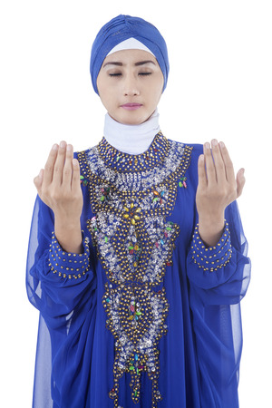 Pretty young muslim woman wearing islamic clothes and praying, isolated on white background photo