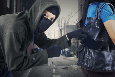 delincuencia: Ladrón que roba un teléfono móvil desde el bolso de una mujer en la calle
