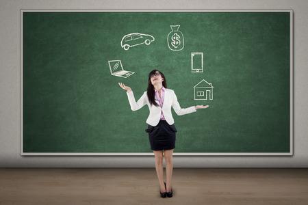 juggling: Businesswoman juggling responsibilities over blackboard in the classroom