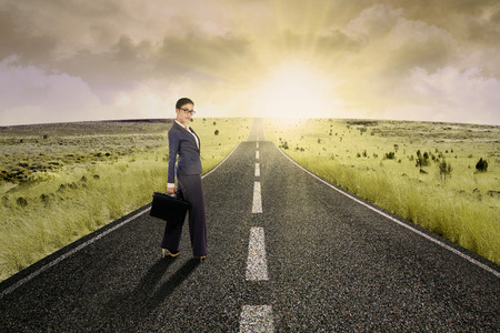 new way: Businesswoman standing on the highway road, symbolizing as the way to the new opportunity