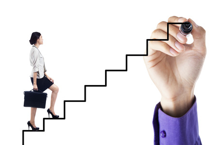Businesswoman stepping up on stairs to gain her success with a hand drawing the stairs photo
