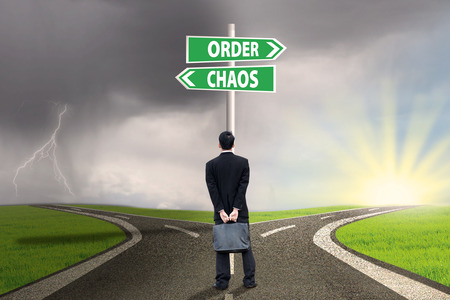 Businessman standing on the road looking at signpost of order and chaos photo