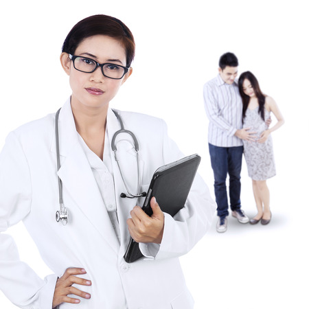 Portrait of pregnant woman and her husband visiting an obstetrician photo