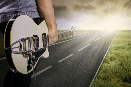 country landscape: The lonely guitarist walking on road, shot outdoors at dusk