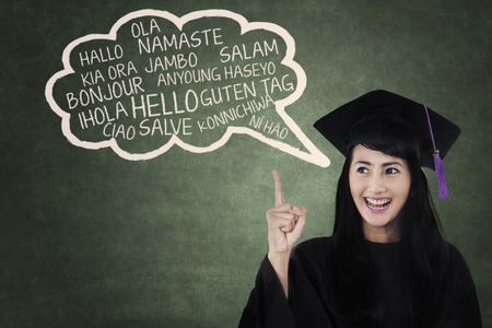 Education concept: female college student in gown learn multilanguage at class Stock Photo