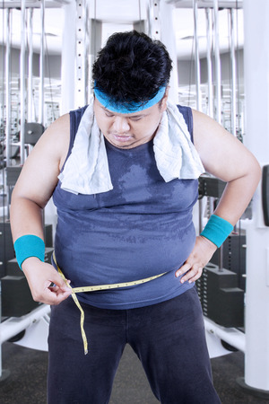 obese man: Obese man measuring his belly in the fitness center