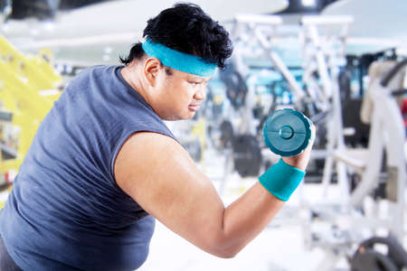 fatness: Fat man exercising with two dumbbells in the fitness center