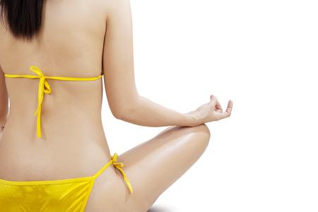 Woman wearing bikini meditating with lotus position. isolated on white background photo