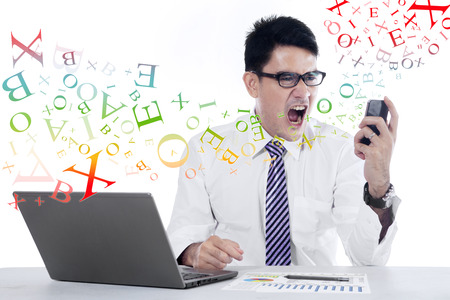 Angry young businessman looking at cell phone in office photo