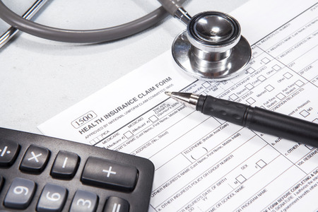 billing: Cost of healthcare concept. Stethoscope, health form, pen, glasses, and calculator.