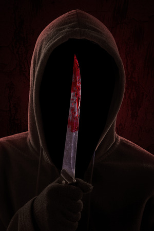 A dangerous hooded man standing in the dark and holding a bloody knife Stock Photo