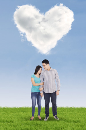 heart under: Happy young couple standing under clouds shaped of heart Stock Photo