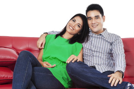 red sofa: Happy couple relaxing on a red sofa over white background Stock Photo