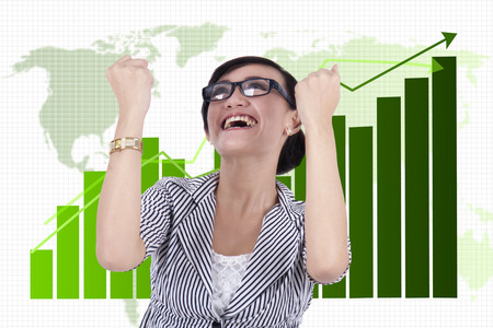 international sales: Businesswoman celebrating success in front of a business graph Stock Photo