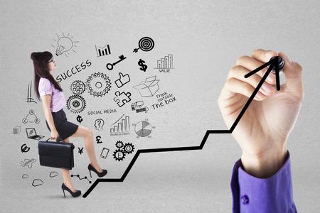 Businesswoman climbing upward chart to gain her business target by following businessman photo
