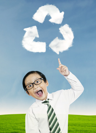 Smiling child pointing at recycle symbol above his head photo