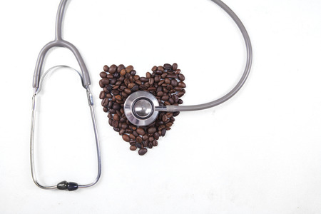 Coffee beans with a stethoscope on white background photo