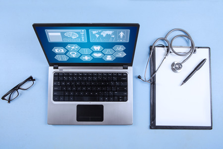 Computer laptop, stethoscope and clipboard with blank paper sheet on the table photo