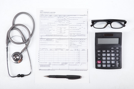 personal record: Cost of healthcare concept. Stethoscope, health form, pen, glasses, and calculator.