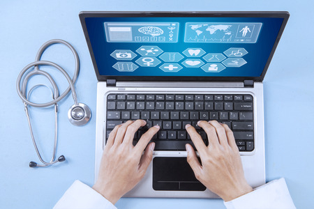 Close up of male doctor working on a laptop for analyzing human illness photo