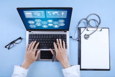 Doctor typing on keyboard to analyze medical report on laptop Banco de Imagens