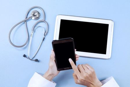 Doctor working with smartphone and digital tablet while touching the screen photo