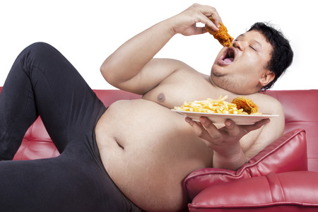 Fat man eats fast food while sitting on sofa at home photo