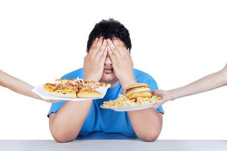 Fat man rejecting to eat junk food. Isolated on white background