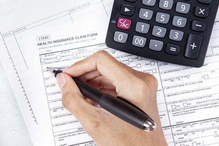 healt: Cost of healthcare concept. Patient filling the healt insurance claim form Stock Photo