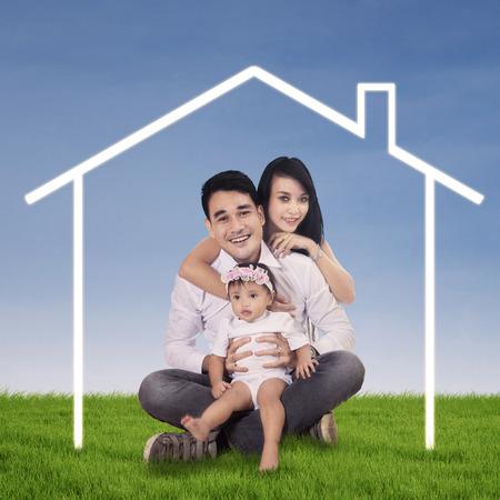 droomhuis: Gelukkige Aziatische familie poseren met hun droomhuis outdoor