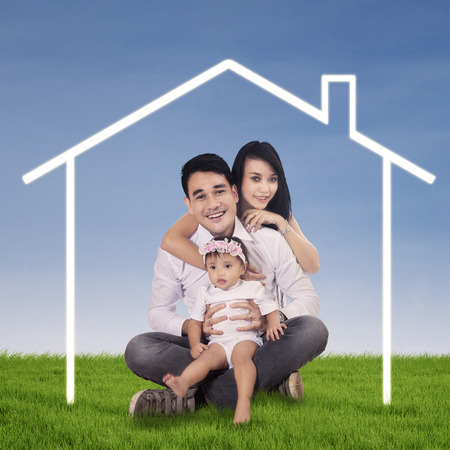 Happy asian family posing with their dream house outdoor photo