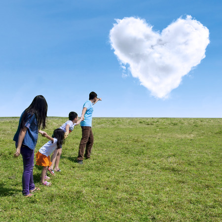 point: Happy family walking in the park with cloud of love in the sky Stock Photo