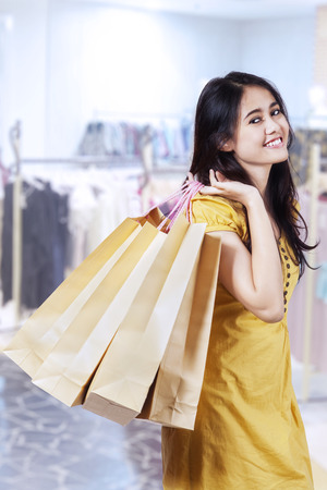 carrying girl: Young beautiful woman with shopping bags in shopping centre