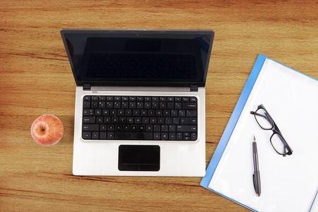 Laptop computer, folder, and apple on a wooden tablet with glasses and a pen photo