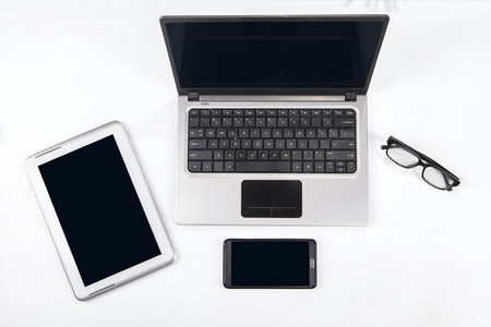 Close up of digital tablet, laptop computer, smartphone, and glasses photo