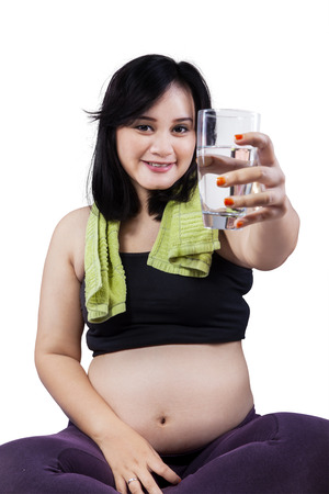 Beautiful pregnant woman sitting on mattress and holding a glass with water photo