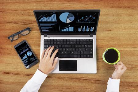 laptop computers: Alto angolo di vista di analisi finanziaria utilizzando il computer portatile Archivio Fotografico