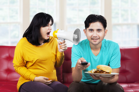 Portrait of angry pregnant woman at her husband in the home photo