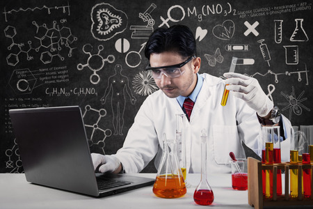 Serious expression of male scientist wearing lab coat and working in laboratory photo