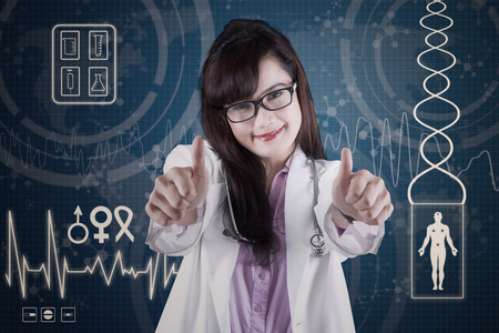 Attractive doctor showing thumbs-up in front of medical background photo