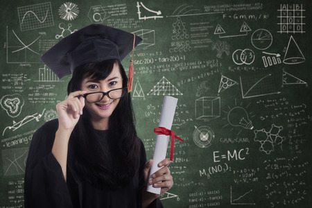 Woman in graduation gown smiling happy in front of blackboard photo