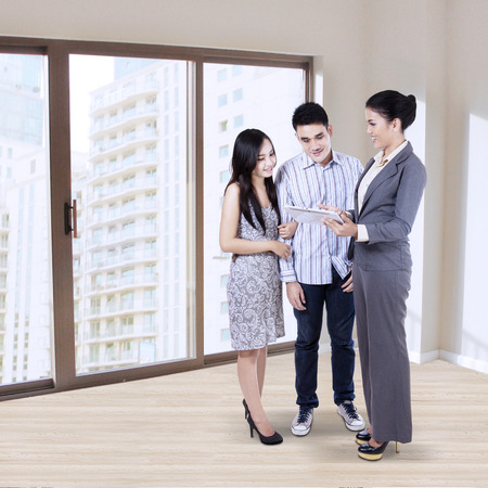 Portrait of a businesswoman explaining something to young family Stock Photo