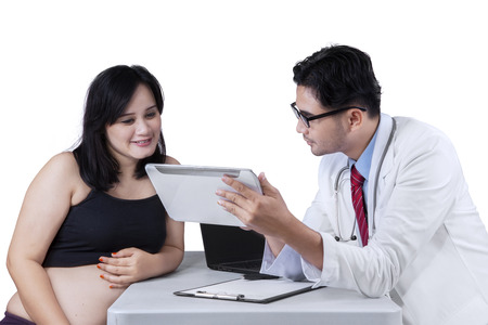 Doctor explaining result test on digital tablet to pregnant woman on digital tablet photo