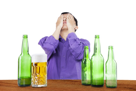 boozer: Drunk man covering his face in the bar, with bottles of beer on the table