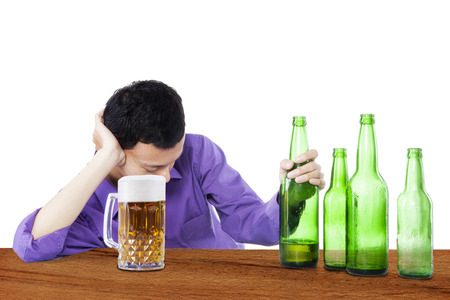 Drunk man sleeping in the bar, with bottle of beer in his hand photo