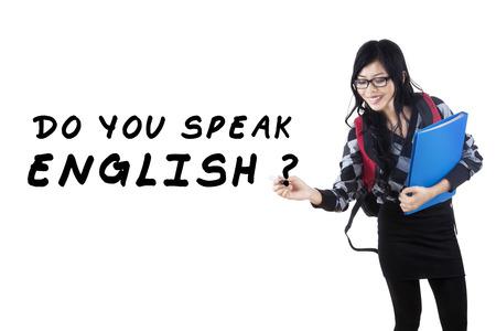 english girl: Learning language concept. Female student write Do You Speak English?